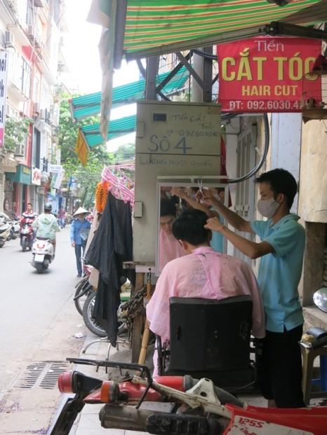 Streetside haircut on the footpath