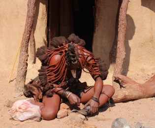 A Himba Tribe women cutting of the traditional ankle bracelets